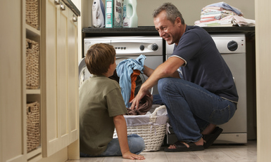 Father and son (9-11) loading washing machine in laundry room